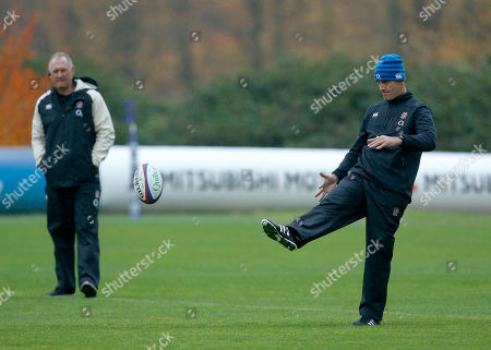 Stock Picture of John Mitchell the England defence coach kicks a ball watched by team manager Richard Hill