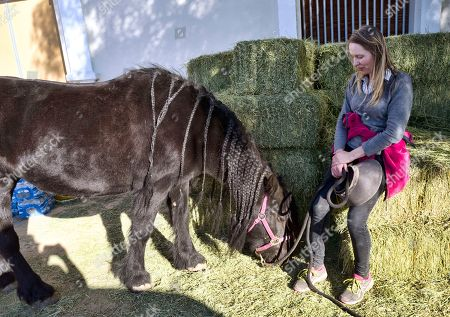 Stock Picture of Wildfire evacuee Eva Loeffler sits with her 20 year-old pony Mini at the Pierce College Equine Center where evacuees are bringing their large and small animals in the Woodland Hills section of Los Angeles on . A wind-driven wildfire raged through Southern California communities on Friday, burning homes and forcing thousands of people to flee as it relentlessly pushed toward Malibu and the Pacific Ocean
