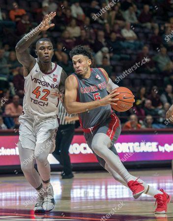 Gardner-Webb guard Jose Perez (5) drives the ball against Virginia Tech guard Ty Outlaw (42) during the first half of an NCAA college basketball game, in Blacksburg, Va. Virginia Tech won 87-59