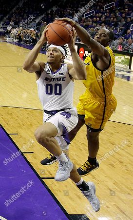Kennesaw State's Kyle Clarke tries to strip the ball away from Kansas State's Mike McGuirl (00) during the second half of an NCAA college basketball game, in Manhattan, Kan. Kansas State won 56-41