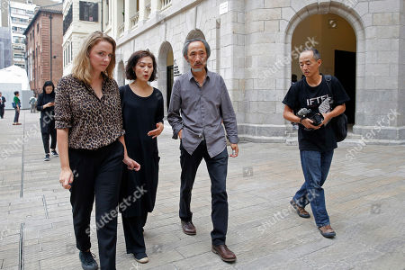 Chinese dissident writer Ma Jian, second from right, walks at the Tai Kwun venue, which is hosting the Hong Kong International Literary Festival, in Hong Kong, . A Hong Kong arts venue has canceled the appearance at a literary festival of exiled Chinese writer Ma Jian, known for his novels criticizing China's ruling Communist Party. Ma tweeted that the Tai Kwun venue, which is hosting the Hong Kong International Literary Festival, said his two scheduled events had been scratched. He said no explanation was given