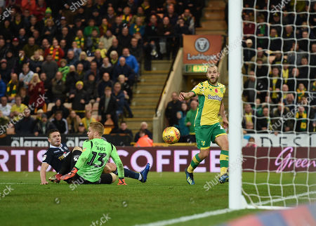 Teemu Pukki of Norwich City looks on as his shot on goal squeezes past Shaun Hutchinson of Millwall and Ben Amos of Millwall for the game-winning goal, 4-3
