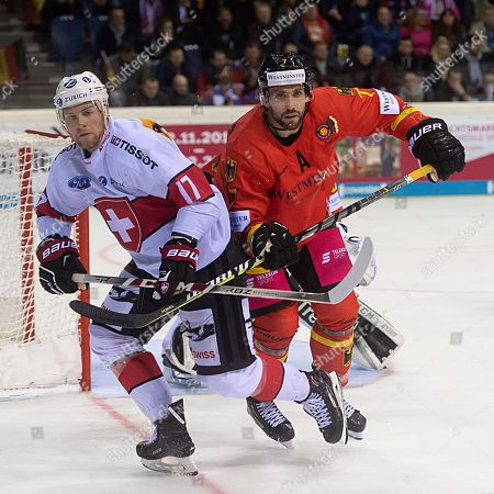 Switzerland's Richard Tanner, left, fights for the puck against Germany's Daryl Boyle, right, during the Ice Hockey Deutschland Cup match between Germany and Switzerland at the Koenig Palast stadium in Krefeld, Germany, 10 November 2018.