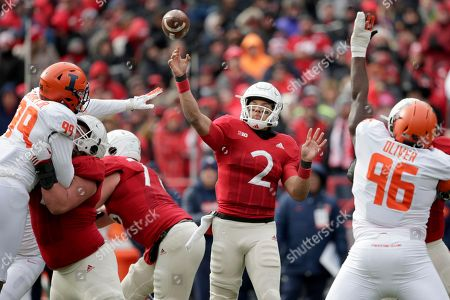 Nebraska quarterback Adrian Martinez (2) throws a pass between Illinois defensive lineman Owen Carney Jr. (99) and defensive lineman Tymir Oliver (96) during the first half of an NCAA college football game in Lincoln, Neb