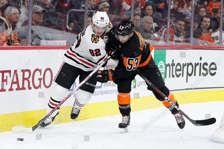 Chicago Blackhawks' Luke Johnson, left, and Philadelphia Flyers' Shayne Gostisbehere, right, battle for the puck during the first period of an NHL hockey game, in Philadelphia. The Flyers won 4-0