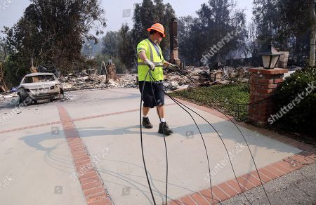 Stock Photo of Frontier Communications worker Kelly Adams clears telephone and TV cable lines at one of at least 20 homes destroyed just on Windermere Drive in the Point Dume area of Malibu, Calif., . Known as the Woolsey Fire, it has consumed thousands of acres and destroyed dozens of homes