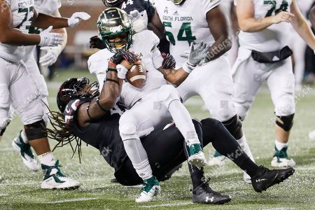 Chris Oladokun, Michael Pitts. South Florida quarterback Chris Oladokun, center, is sacked by Cincinnati defensive end Michael Pitts, during the second half of an NCAA college football game, in Cincinnati