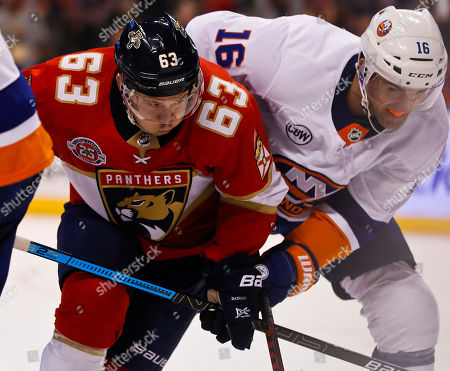 Nick Bjugstad, Evgenii Dadonov, Andrew Ladd. Florida Panthers right wing Evgenii Dadonov, left, and New York Islanders left wing Andrew Ladd go for the puck during the second period of an NHL hockey game, in Sunrise, Fla