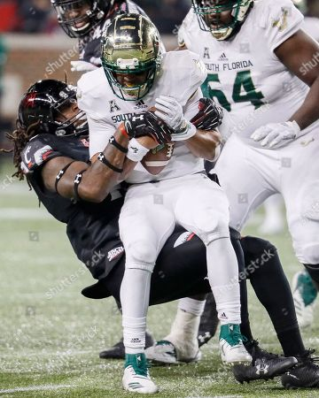 Stock Image of Chris Oladokun, Michael Pitts. South Florida quarterback Chris Oladokun, center, is sacked by Cincinnati defensive end Michael Pitts, during the second half of an NCAA college football game, in Cincinnati