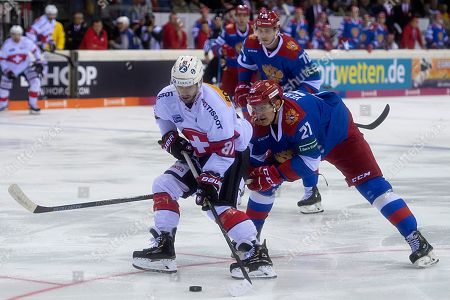 Switzerland's Jason Fuchs (L) fights for the puck against Russia's Andrei Yermakov during the Ice Hockey Deutschland Cup match between Switzerland and Russia at the Koenig Palast stadium in Krefeld, Germany, 11 November 2018.