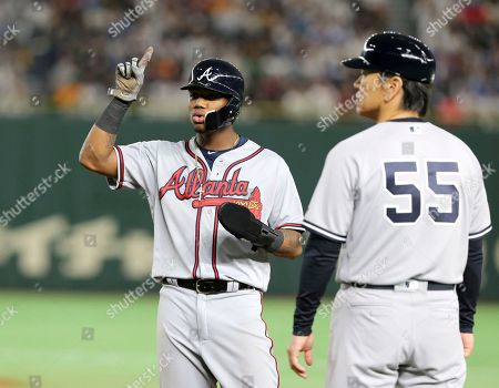 Stock Photo of MLB All-Star Ronald Acuna Jr. of the Atlanta Braves points to the ceiling while talking with first base coach Hideki Matsui (55) after teammate Juan Soto of the Washington Nationals ground-rule flied out in the fourth inning of Game 3 against All Japan at the All-Stars Series baseball at Tokyo Dome in Tokyo