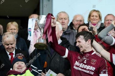 Ballycran vs Cushendall. Cushendall's Paddy Burke raises the cup with supporter John McKillop
