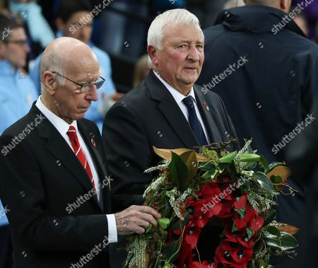 Former Manchester United Legend Sir Bobby Charlton and Manchester City Great Mike Summerbee lay a poppy wreath on the pitch before Kick Off on Remembrance Sunday