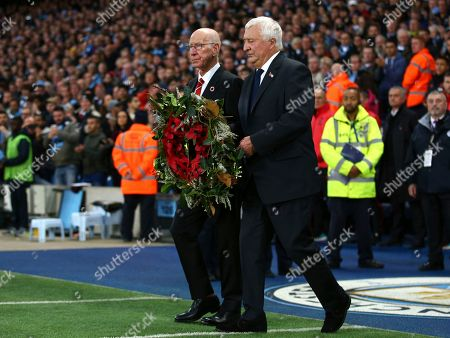 Sir Bobby Charlton, left, and Mike Summerbee carry out a wreath before kick-off in the English Premier League soccer match between Manchester City and Manchester United at the Etihad stadium in Manchester, England
