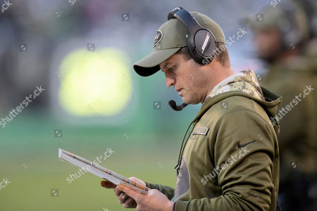 New York Jets offensive coordinator Jeremy Bates looks at charts during the second half of an NFL football game against the Buffalo Bills, in East Rutherford, N.J