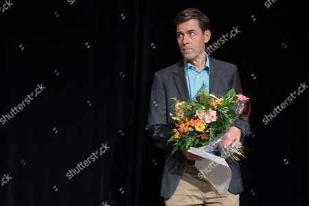 Swiss writer Peter Stamm holds flowers at the Swiss Book Prize ceremony after receiving the award for his book 'Die sanfte Gleichgueltigkeit der Welt' (The gentle indifference of the world) at the Theater Basel, in Basel, Switzerland, 11 November 2018.