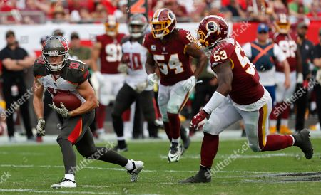Tampa Bay Buccaneers wide receiver Adam Humphries (10) runs against the Washington Redskins' inside linebacker Zach Brown (53) and inside linebacker Mason Foster (54) after a reception during the second half of an NFL football game, in Tampa, Fla