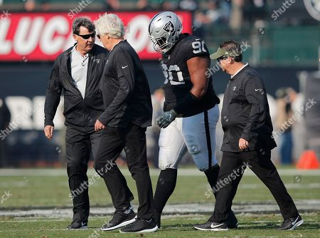 Oakland Raiders defensive tackle Johnathan Hankins (90) walks off the field with trainers during the first half of an NFL football game against the Los Angeles Chargers in Oakland, Calif