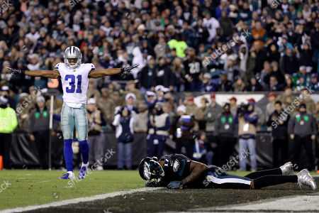 Philadelphia Eagles wide receiver Alshon Jeffery, right, lies on the ground after missing a catch as Dallas Cowboys cornerback Byron Jones (31) reacts to the play during the second half of an NFL football game, in Philadelphia