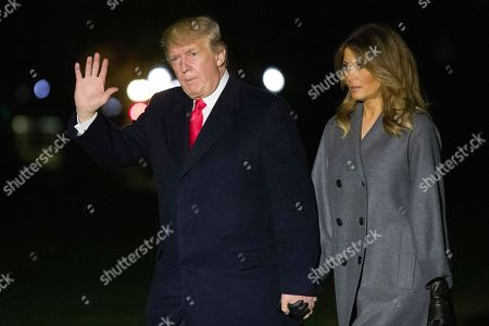 Donald Trump, Melania Trump. President Donald Trump waves as he walks with first lady Melania Trump, after stepping off Marine One, on the South Lawn of the White House, in Washington. Trump is returning from a trip to Paris