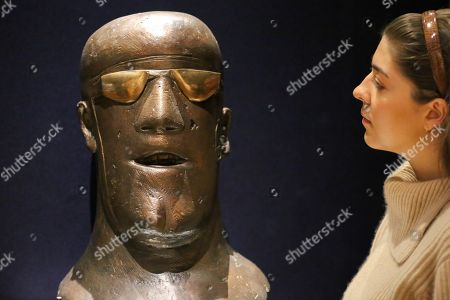"""A member of staff looks at """"Head"""", conceived in 1967 by Dame Elisabeth Frink R.A. (British, 1930-1993) signed and numbered 'Frink 3/6' (at the base of the neck) bronze with a brown patina and polished goggles - (Estimate £100,000-150,000)."""