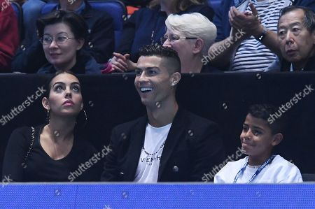Juventus' Portuguese forward Cristiano Ronaldo (C) sits with Georgina Rodriguez (L) and his son Cristiano Jr (R) as they watch the game between US player John Isner against Serbia's Novak Djokovic during their men's singles round-robin match on day two of the ATP World Tour Finals tennis tournament at the O2 Arena in London, Britain, 12  November 2018.