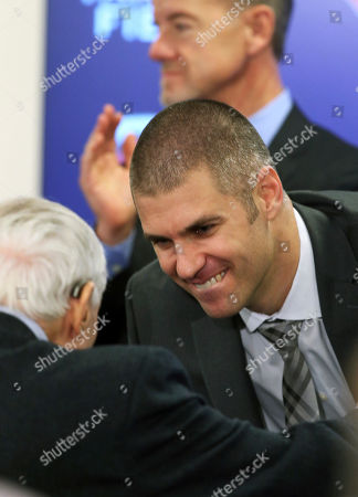 Minnesota Twins' Joe Mauer, right, talks with columnist Sid Hartman as Twins owner Jim Pohlad, top, applauds after Mauer's baseball retirement news conference, in Minneapolis, after 15 major league seasons, all with the Twins