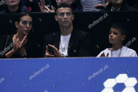 Cristiano Ronaldo, center, with his partner Georgina Rodriguez, and his son Cristiano Ronaldo Jr watches as Novak Djokovic of Serbia plays John Isner of the United States in their ATP World Tour Finals singles tennis match at the O2 Arena in London