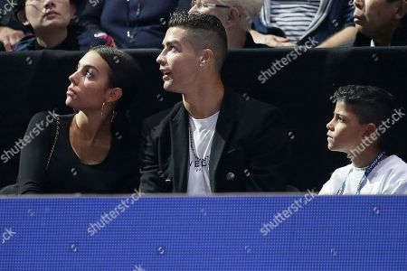 Cristiano Ronaldo, center, with his partner Georgina Rodriguez, and his son Cristiano Ronaldo Jr watch a screen as Novak Djokovic of Serbia plays John Isner of the United States in their ATP World Tour Finals singles tennis match at the O2 Arena in London