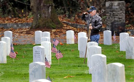 U.S. Navy veteran James Grout salutes his uncle's grave on the observed Veterans Day holiday at the Fort Lawton Post Cemetery, in Seattle. Grout makes the rounds of several cemeteries every Veterans Day to honor veteran friends and family members