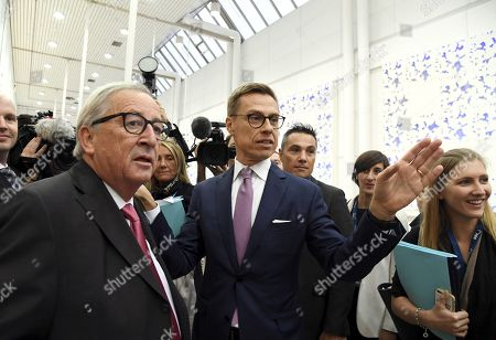 A candidate to lead EPP, Alexander Stubb of Finland speaks with President of the European Commission Jean-Claude Juncker (L) at the European People's Party (EPP) congress
