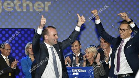 The lead candidates of the EPP, Manfred Weber of Germany and Alexander Stubb of Finland (R) gesture after the results of the EPP lead candidate voting at the session of the European People's Party (EPP) congress