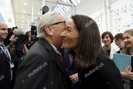 President of the European Commission Jean-Claude Juncker (L) kisses Suzanne Innes-Stubb, wife of lead candidate Alexander Stubb from Finland at the European People's Party (EPP) congress