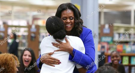 "Former first lady Michelle Obama embraces a student at her alma mater, Whitney M. Young Magnet High School, on Chicago's West Side, a day before the launch of a book tour to promote her memoir, ""Becoming"