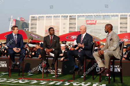 Steve Young, from left, Randy Moss, Matt Hasselbeck and Charles Woodson speak on a pre-game talk show set before an NFL football game between the San Francisco 49ers and the New York Giants in Santa Clara, Calif