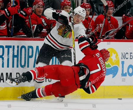 Carolina Hurricanes' Phillip Di Giuseppe (7) collides with Chicago Blackhawks' Luke Johnson (62) during the second period of an NHL hockey game, in Raleigh, N.C