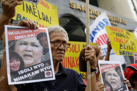 """Martial law victim Danny Dela Fuente holds an image of former first lady Imelda Marcos with her son, Ferdinand """"Bongbong"""" Marcos Jr. and daughter Imee Marcos, as they hold a rally outside the special anti-graft Sandiganbayan court in metropolitan Manila, Philippines, calling for the arrest of Imelda on . A Philippine court recently found Imelda Marcos guilty of graft and ordered her arrest last week in a rare conviction among many corruption cases that she's likely to appeal to avoid jail and losing her seat in Congress"""