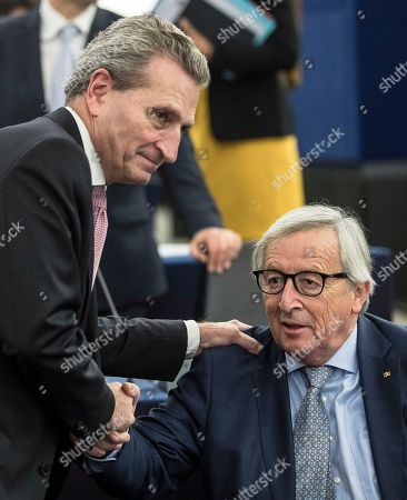Gunther Oettinger, EU Commissioner for Budgetand Human Resources, left, shakes hands with European Commission President Jean-Claude Juncker at the European Parliament in Strasbourg, eastern France, Tuesday, Nov.13, 2018