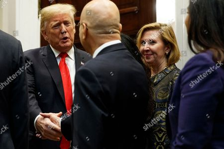 """Stock Photo of Donald Trump, Mira Ricardel. Deputy National Security Adviser Mira Ricardel, right, watches as President Donald Trump arrives for a Diwali ceremonial lighting of the Diya in the Roosevelt Room of the White House, in Washington. In an extraordinary move, first lady Melania Trump is publicly calling for the dismissal of Ricardel. After reports circulated that the president had decided to remove Ricardel, the first lady's spokeswoman issued a statement saying: """"It is the position of the Office of the First Lady that she no longer deserves the honor of serving in this White House."""" Ricardel is national security adviser John Bolton's deputy"""