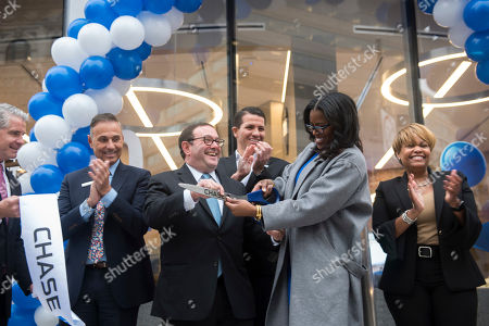 From left, Chase employees Dan Deegan, Steven Vachon, Peter Scher, Jonerik Wilson, Thasunda Duckett and Stephanie Jones celebrate after cutting the ribbon at the Grand Opening of Chase's first retail branch in Greater Washington at McPherson Square, in Washington. Chase will open up to 70 new branches and hire up to 700 new people in the region. All entry-level employees will earn no less than $18/hourly