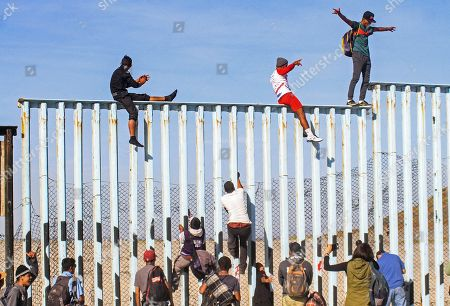Members of the caravan of Central American migrants climb the border wall in Tijuana, Baja California, Mexico, 13 November 2018. Dozens of Central American migrants reached the US-Mexico border, and some climbed the fence that divides both countries, a first step in their final goal of entering the United States.