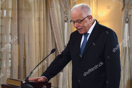 New Tunisian Civil Servents minister Kamel Morjane takes oath in Tunis, Wednesday, Nov.14, 2018. The reshuffled government of Tunisian Prime Minister Youssef Chahed has passed a parliamentary vote of confidence last Monday