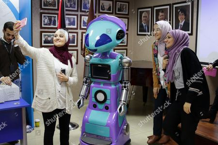 Visitors take a selfie with 'Zain Robot 079' during the Jordanian Robot 2018 Exhibit, in Amman, Jordan, 14 November 2018. The Jordanian Robot 2018 Exhibit was organized by the Arab Innovation and the Association and the Talal Abu Ghazaleh University college for Innovation.