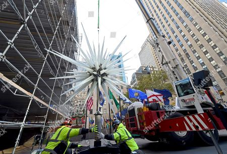 IMAGE DISTRIBUTED FOR TISHMAN SPEYER - Workers prepare to raise the 2018 Swarovski Star to the top of the 72-foot Rockefeller Center Christmas tree, in New York. The iconic star has been reimagined by architect Daniel Libeskind and features 3 million Swarovski crystals on 70 illuminated spikes. The 86th Rockefeller Center Christmas Tree Lighting ceremony will take place on Wednesday, Nov. 28