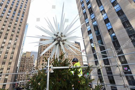 IMAGE DISTRIBUTED FOR TISHMAN SPEYER - A worker secures the 2018 Swarovski Star to the top of the Rockefeller Center Christmas tree, in New York. The iconic star has been reimagined by architect Daniel Libeskind and features 3 million Swarovski crystals on 70 illuminated spikes. The 86th Rockefeller Center Christmas Tree Lighting ceremony will take place on Wednesday, Nov. 28