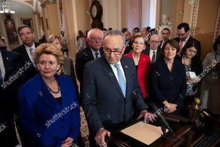 Chuck Schumer, Debbie Stabenow, Tammy Baldwin, Bernie Sanders, Elizabeth Warren, Amy Klobuchar. Senate Minority Leader Chuck Schumer, D-N.Y., is surrounded by the Senate Democratic Caucus as he talks to reporters at the Capitol in Washington, . From left are, Sen. Mark Warner, D-Va., Sen. Debbie Stabenow, D-Mich., Sen. Tammy Baldwin, D-Wis., Sen. Bernie Sanders, I-Vt., Sen. Elizabeth Warren, D-Mass., and Sen. Amy Klobuchar, D-Minn