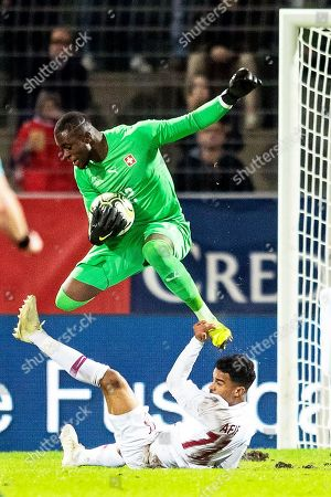 Switzerland's goalkeeper Yvon Mvogo (up) in action against Qatar's Akram Afif (bottom) during the International Friendly soccer match between Switzerland and Qatar in Lugano, Switzerland, 14 November 2018.