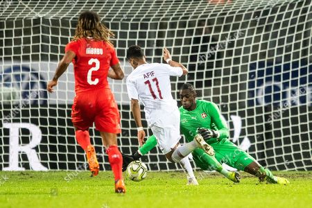 Qatar's Akram Afif (C) scores the 1-0 lead against Switzerland's Kevin Mbabu (L) and goalkeeper Yvon Mvogo (R) during the International Friendly soccer match between Switzerland and Qatar in Lugano, Switzerland, 14 November 2018.