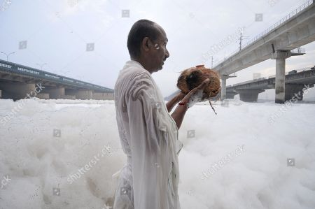 A devotee in the polluted waters of Yamuna river at Kalindi Kunj pays obeisance to the sun god on the occasion of Chhath Puja.