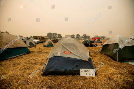 A sign hangs beside a tent at a makeshift shelter for evacuees of the Camp Fire in Chico, Calif., on